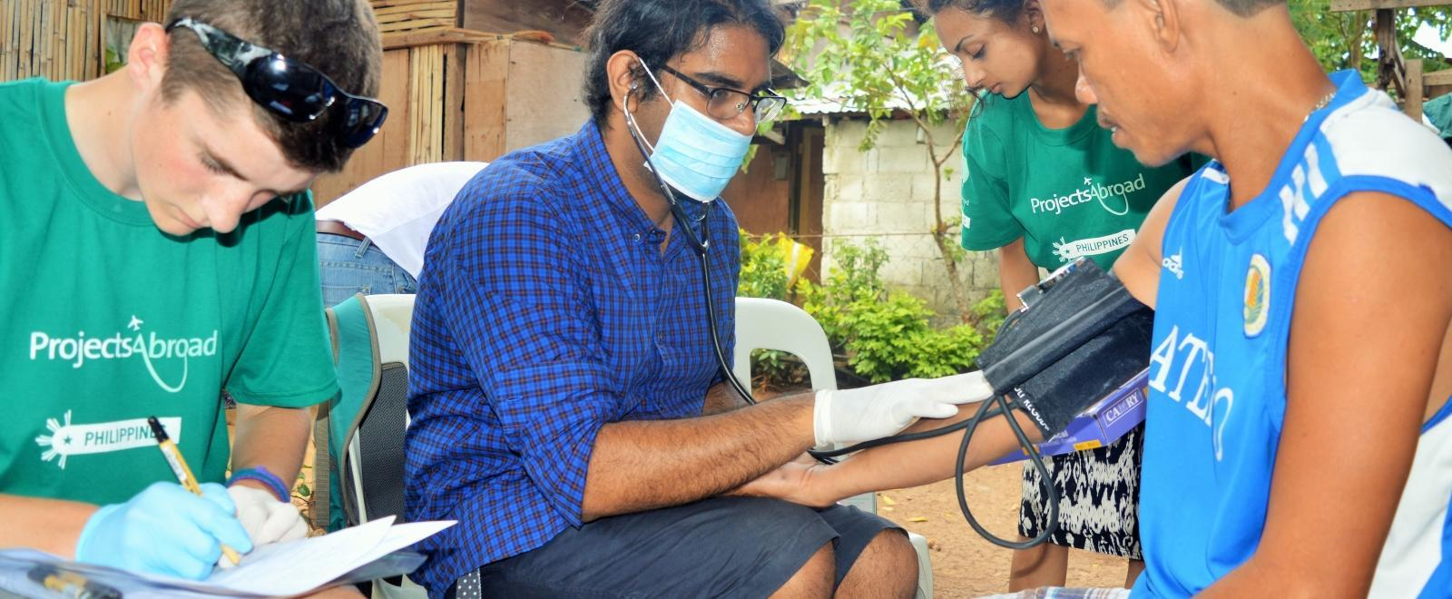 As part of the Projects Abroad Public Health Internship for teenagers in the Philippines, student assists a local doctor during a medical outreach.